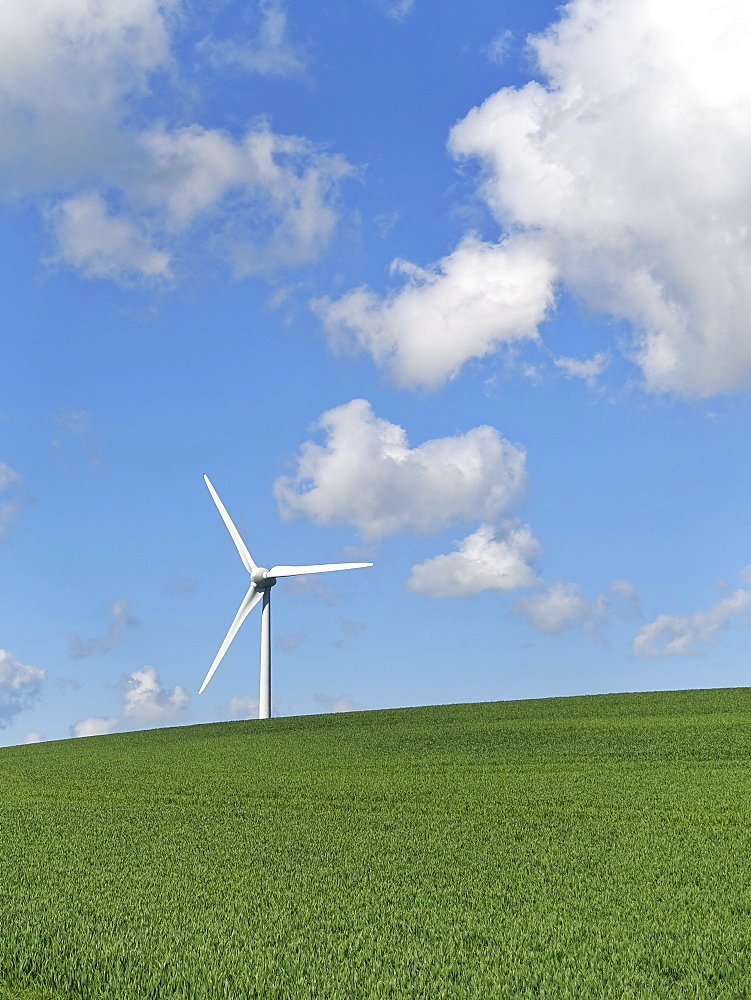 A wind turbine on the brow of a hill under a blue sky with light cloud.