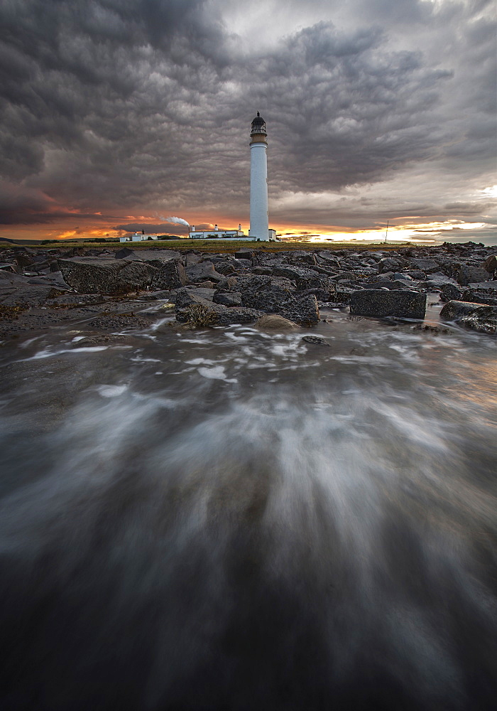 A lighthouse in front of a moody sky.