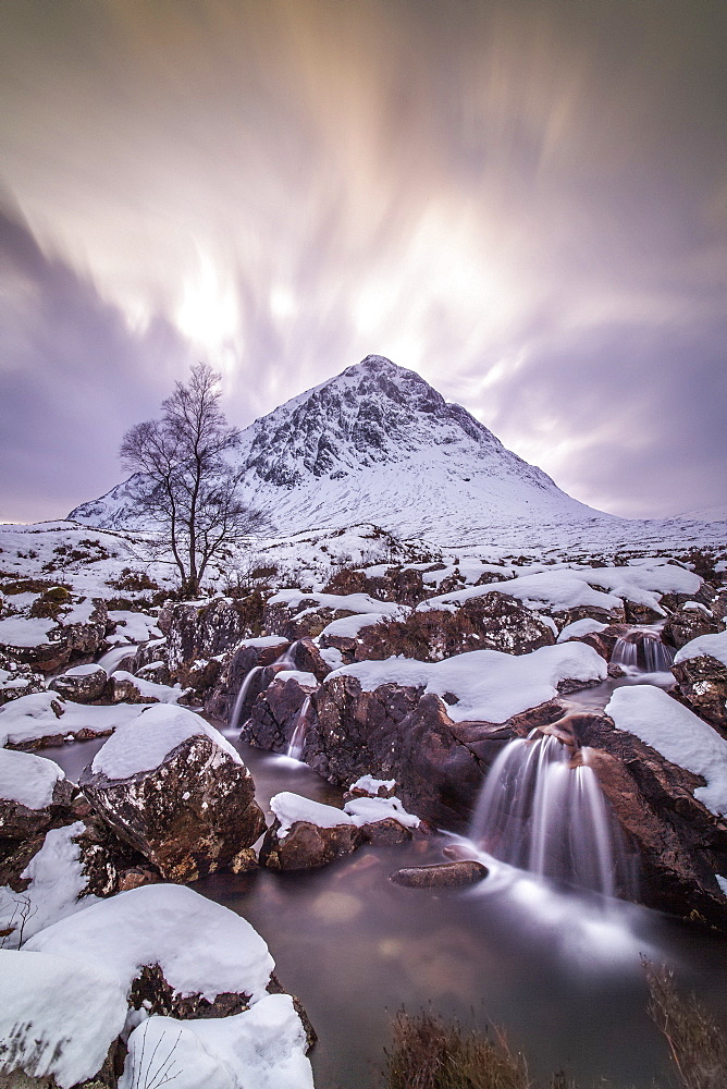 A waterfall in a snowy landscape with a hill behind.