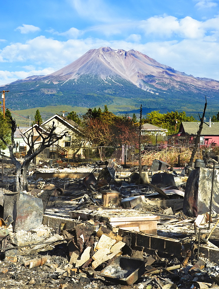 The debris of a burnt down house in a rural landscape, with a mountain in the distance.