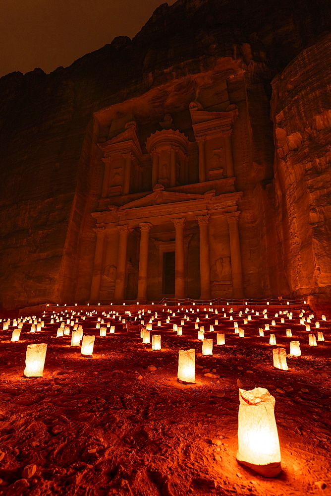 Exterior view of the rock caves and architecture of the facade in sandstone at Al Khazneh or The Treasury at Petra, Jordan at night, A red glow with small glowing lamps on the ground, Petra, Jordan