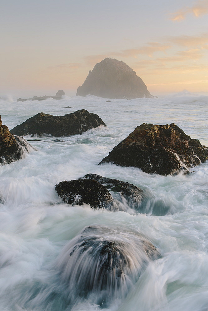 Seascape with breaking waves over rocks at dusk.
