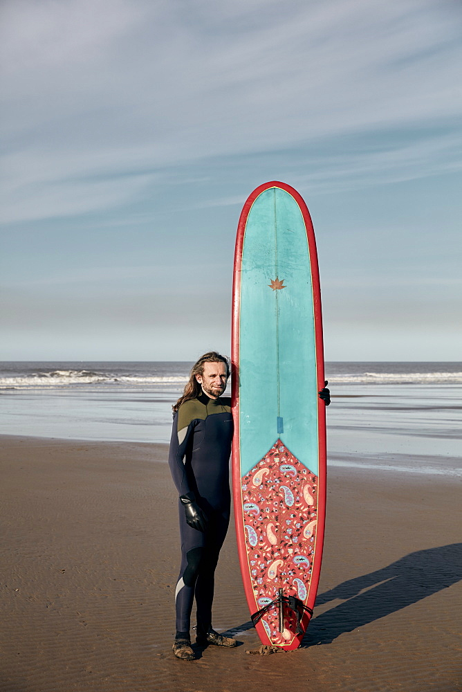 Portrait of a man holding a decorated surf board on a sandy beach, United Kingdom