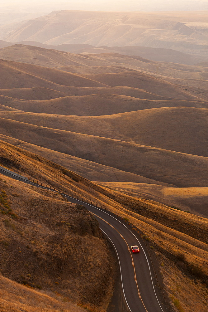 A view looking down of a car moving on a highway at sunrise near Lewiston, Idaho USA, United States of America