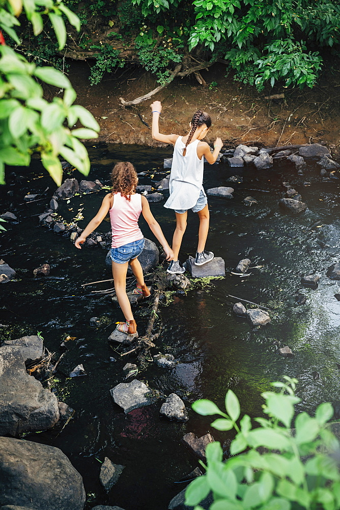 Girls using stones to cross creek, United States of America