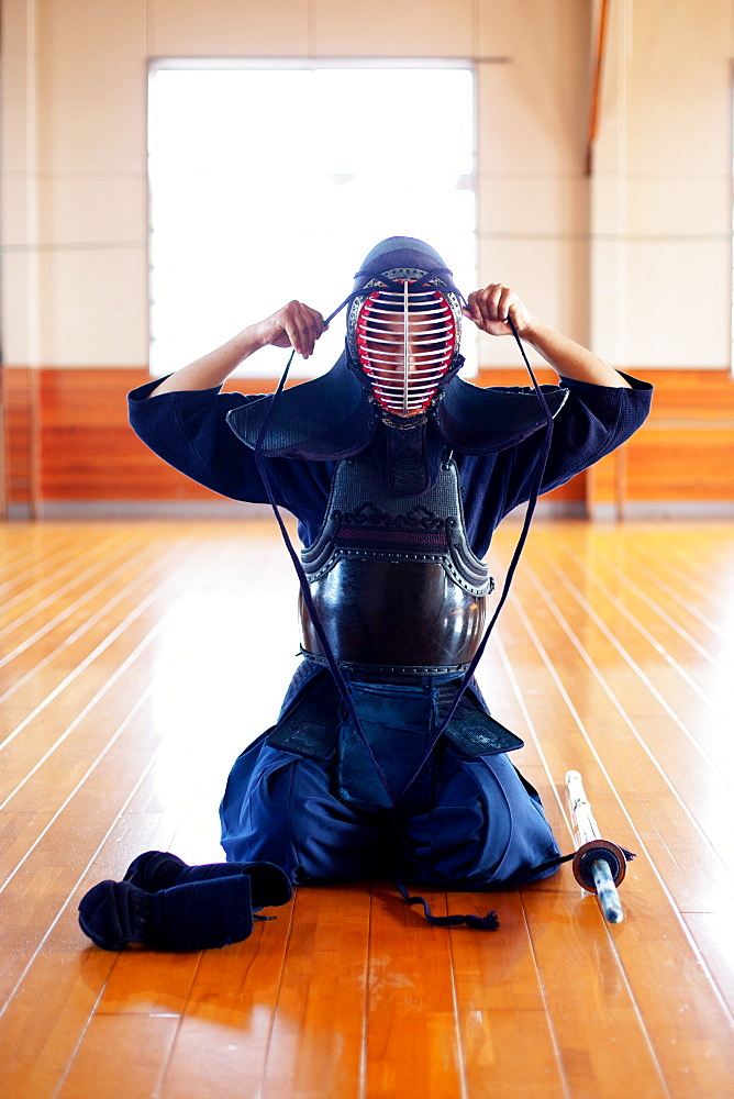 Female Japanese Kendo fighter kneeling on wooden floor, fastening Kendo mask, Kyushu, Japan