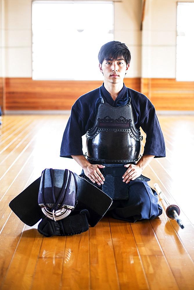 Male Japanese Kendo fighter kneeling on wooden floor, looking at camera, Kyushu, Japan