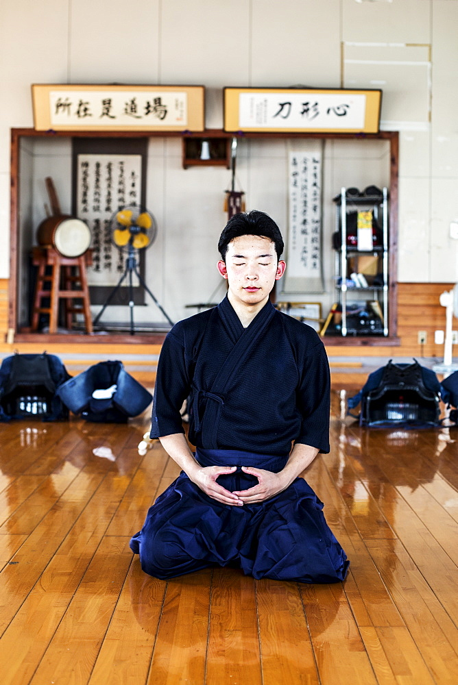 Male Japanese Kendo fighter kneeling on wooden floor, meditating, Kyushu, Japan