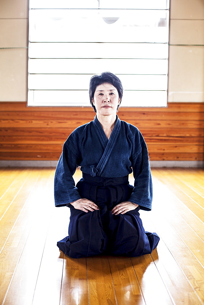 Female Japanese Kendo fighter kneeling on wooden floor, looking at camera, Kyushu, Japan