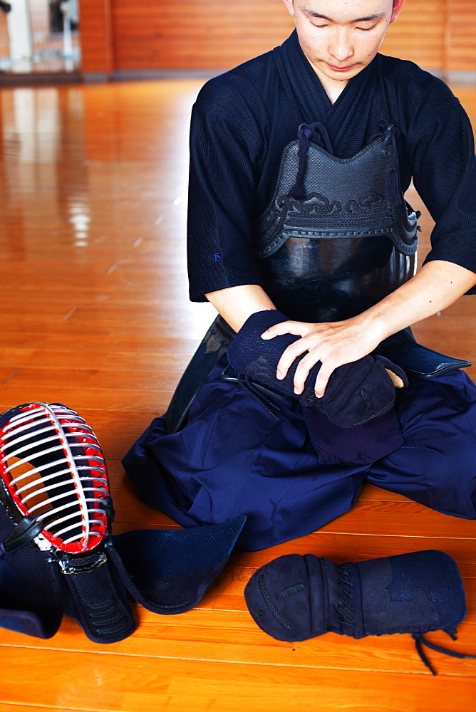 Male Japanese Kendo fighter kneeling on wooden floor, putting on Kote, hand protectors, Kyushu, Japan