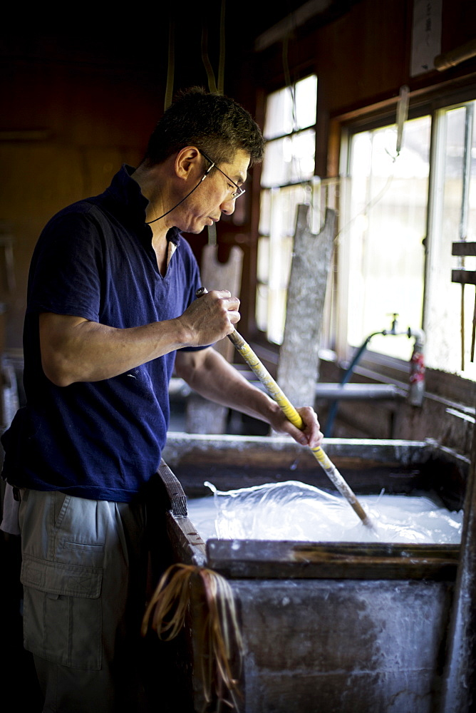 Japanese man stirring a vat of liquid in a workshop with a stick, making traditional Washi paper, Kyushu, Japan