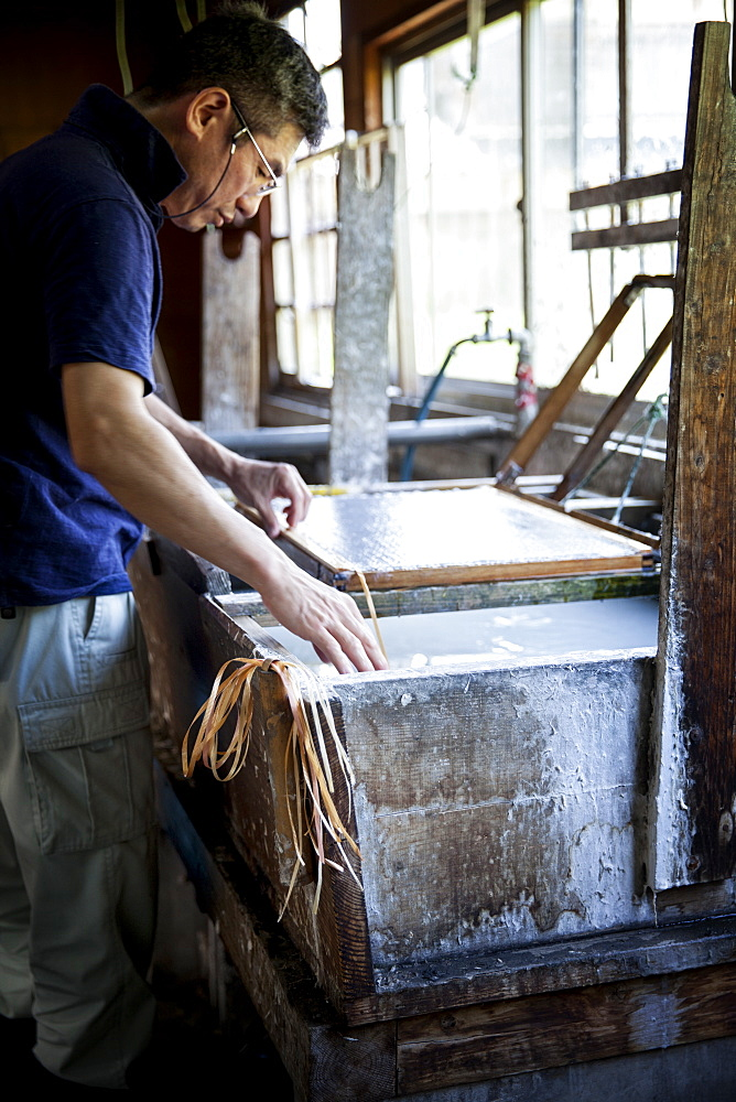 Japanese man in a workshop, holding a wooden frame with pressed pulp, making traditional Washi paper, Kyushu, Japan