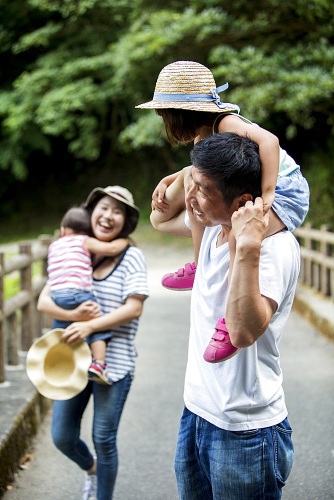 Japanese girl, smiling woman holding hat and man carrying toddler on his shoulders standing on wooden bridge, Kyushu, Japan - 1174-4882