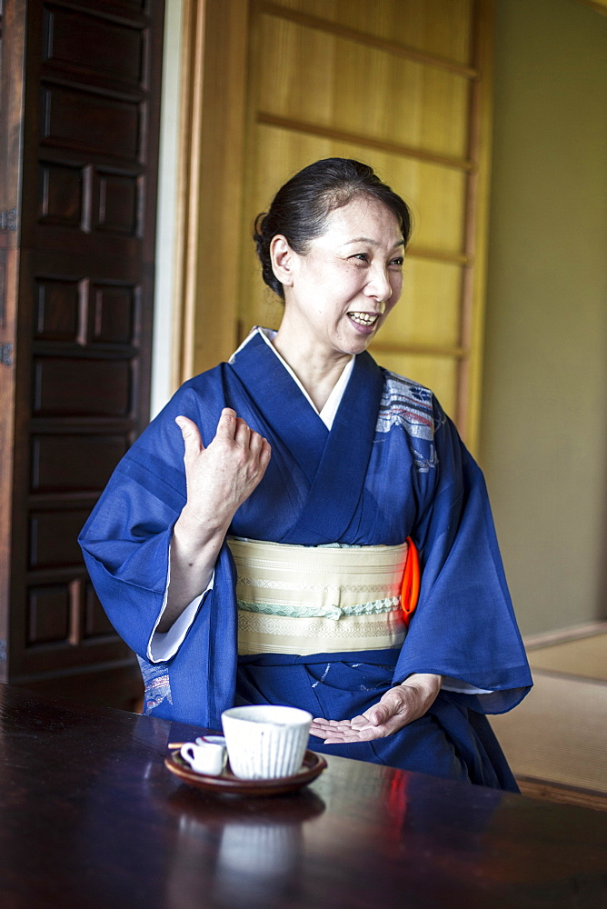 Smiling Japanese woman wearing blue kimono sitting on floor in traditional Japanese house, Kyushu, Japan