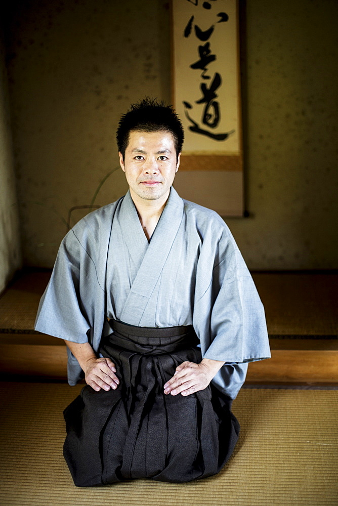 Japanese man wearing kimono sitting on floor in traditional Japanese house, looking at camera, Kyushu, Japan
