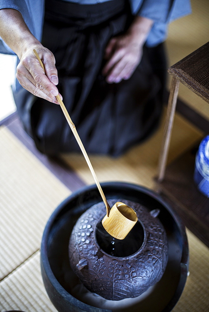 High angle close up of traditional Japanese Tea Ceremony, man using a Hishaku, a bamboo ladle, to pour hot water, Kyushu, Japan