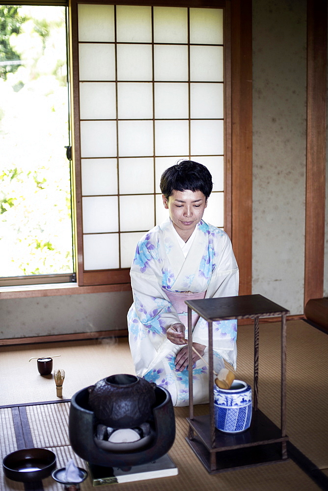 Japanese woman wearing traditional white kimono with blue floral pattern kneeling on tatami mat during tea ceremony, Kyushu, Japan