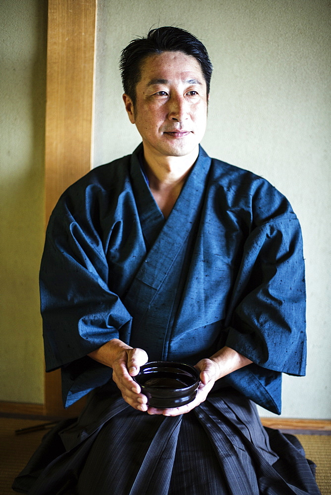 Japanese man wearing kimono kneeling on floor, holding tea bowl during tea ceremony, Kyushu, Japan