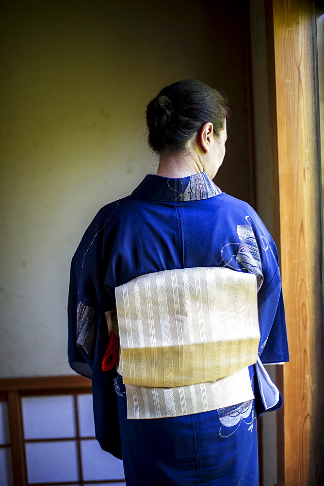 Rear view of Japanese woman wearing traditional bright blue kimono with cream coloured obi, Kyushu, Japan