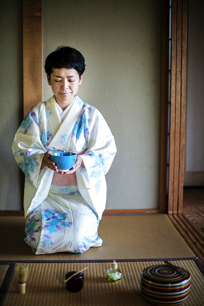 Japanese woman wearing traditional white kimono with blue floral pattern kneeling on floor during tea ceremony, holding blue tea bowl, Kyushu, Japan