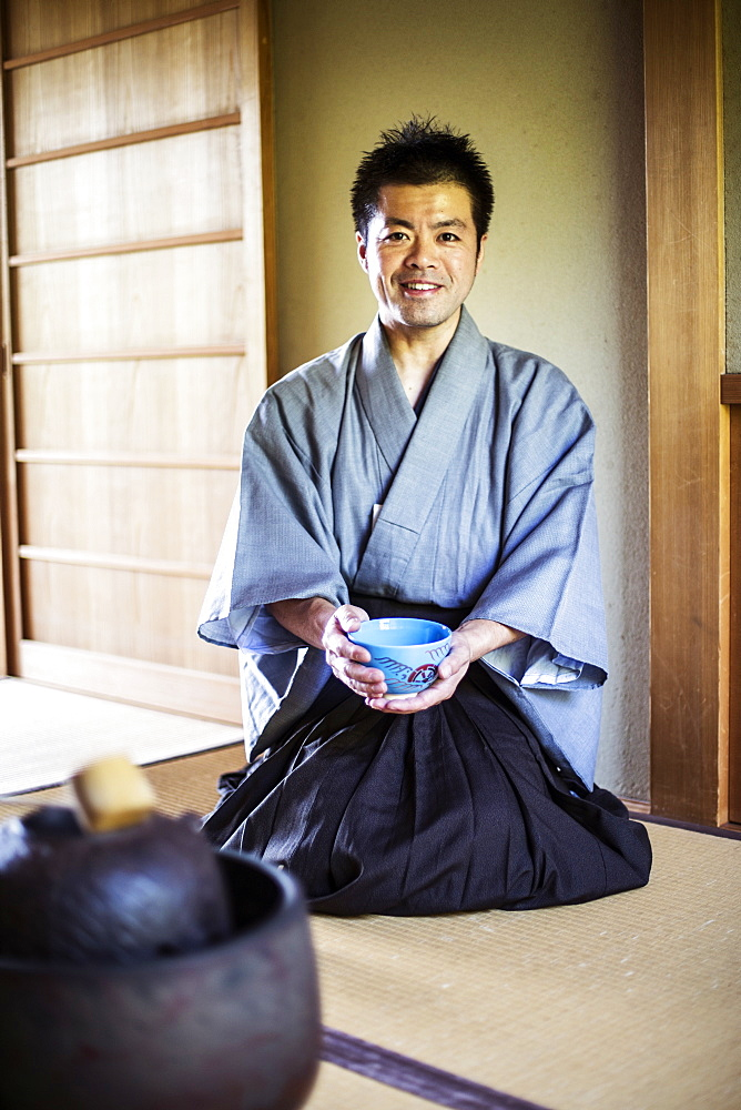 Japanese man wearing traditional kimono kneeling on floor, holding blue tea bowl during tea ceremony, Kyushu, Japan