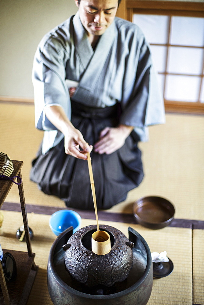 Traditional Japanese Tea Ceremony, man wearing kimono sitting on floor, using a Hishaku, a bamboo ladle, to pour hot water, Kyushu, Japan