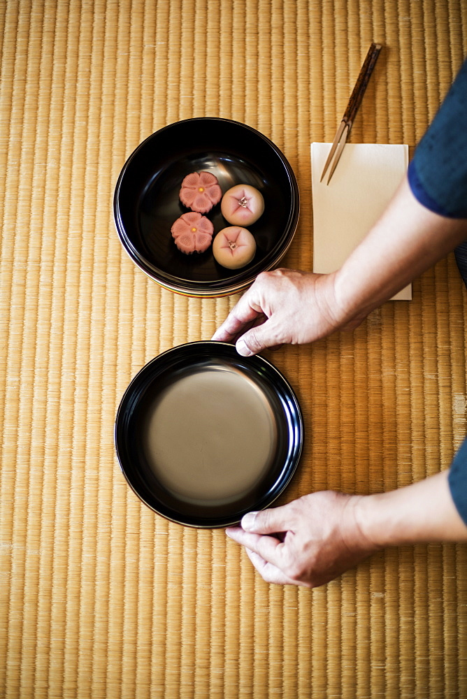 High angle close up of man knelling on floor, holding a bowl with Wagashi, sweets traditionally served during a Japanese Tea Ceremony, Kyushu, Japan
