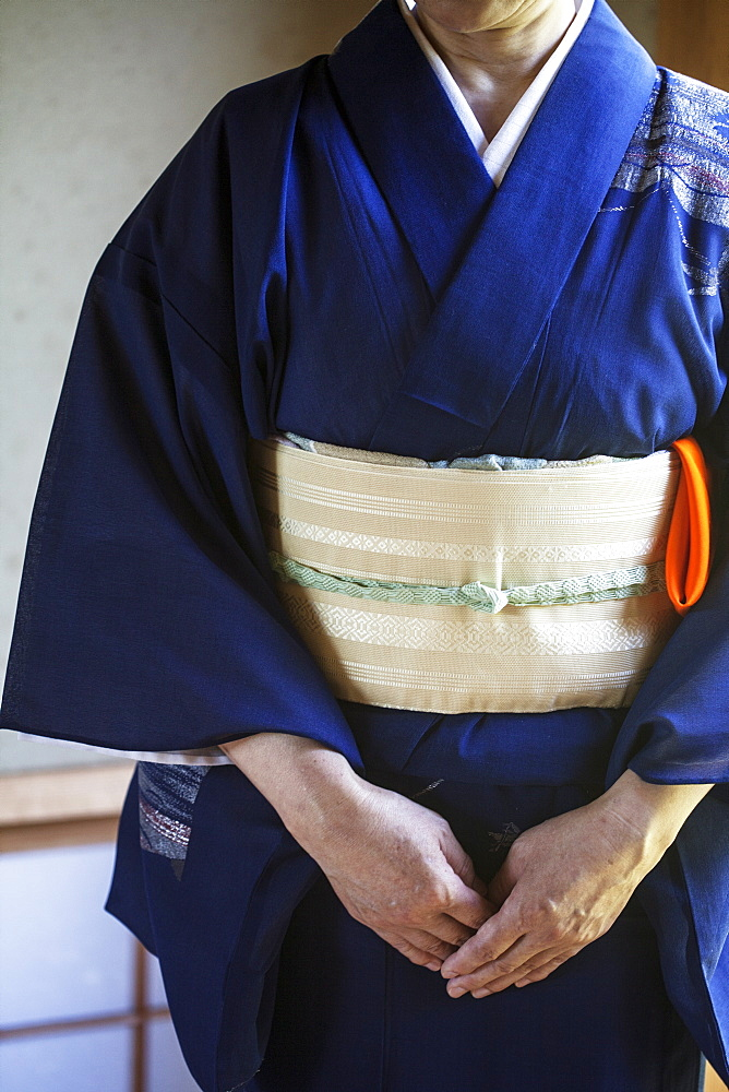 Close up of Japanese woman wearing traditional bright blue kimono with cream coloured obi kneeling on floor, Kyushu, Japan