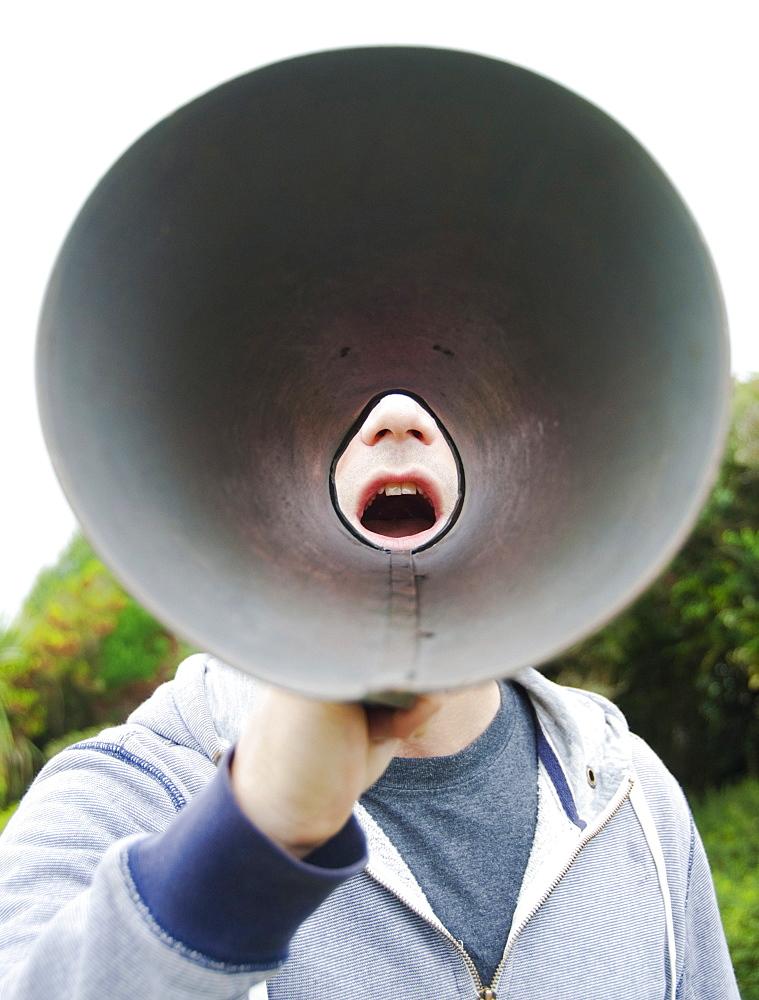 A man using a megaphone in the open air.