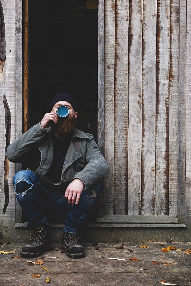 Bearded man sitting in doorway of wooden workshop, drinking tea from blue mug, Berkshire, England