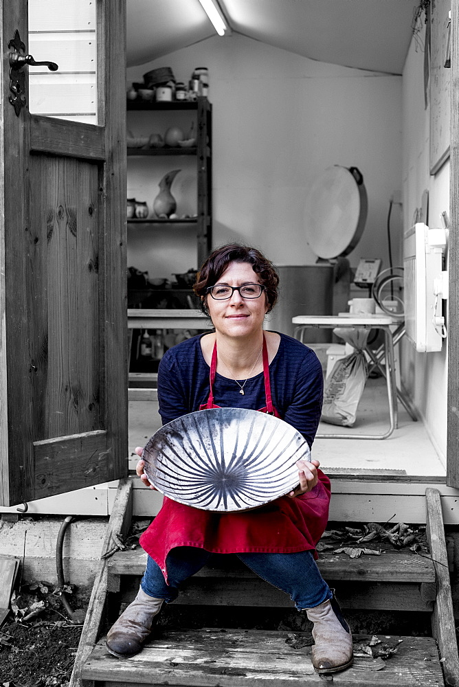 Woman wearing red apron sitting on steps outside her workshop, holding ceramic bowl with black line pattern, England