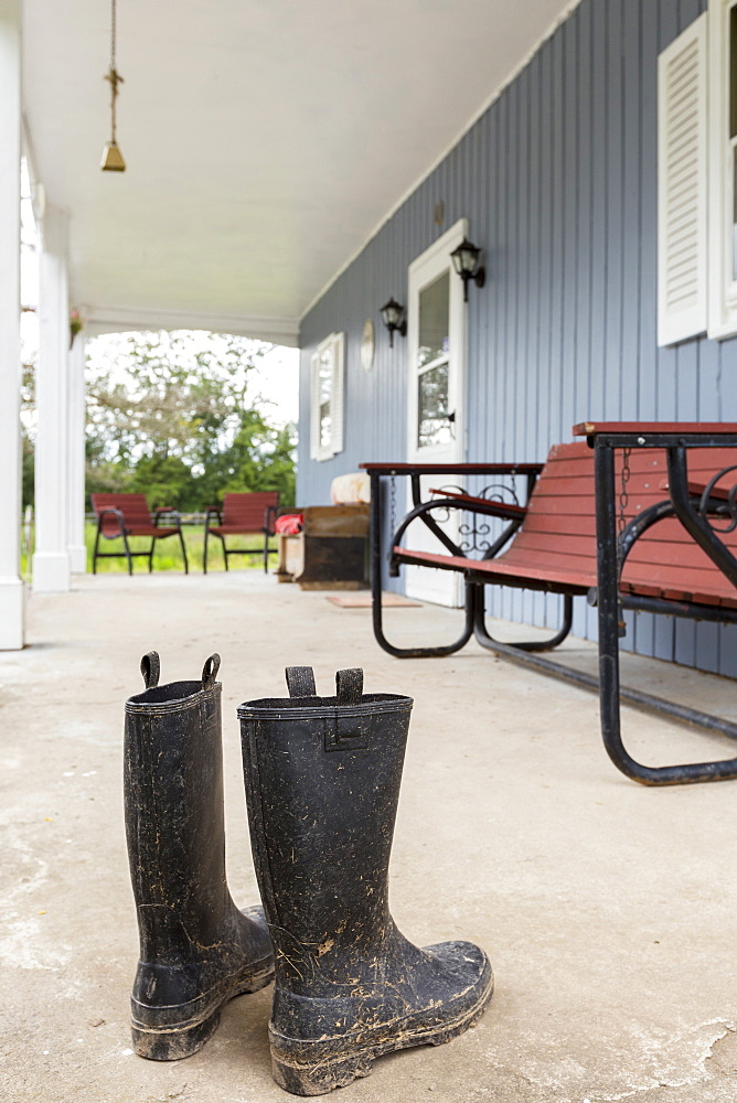 Dirty wellingtons on front porch, Mendon, New York, USA