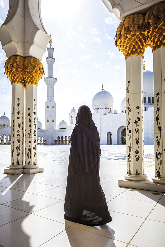 Woman walking at Sheikh Zayed Grand Mosque, Abu Dhabi, United Arab Emirates