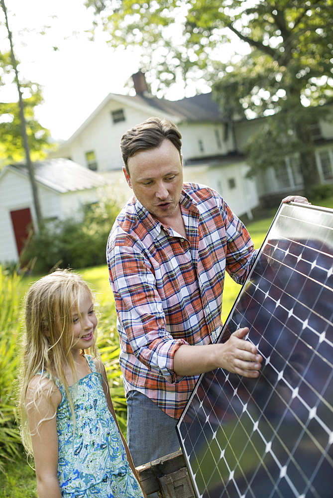 A man and a young girl looking at a solar panel in a garden.