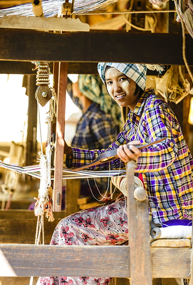 Asian girl weaving fabric