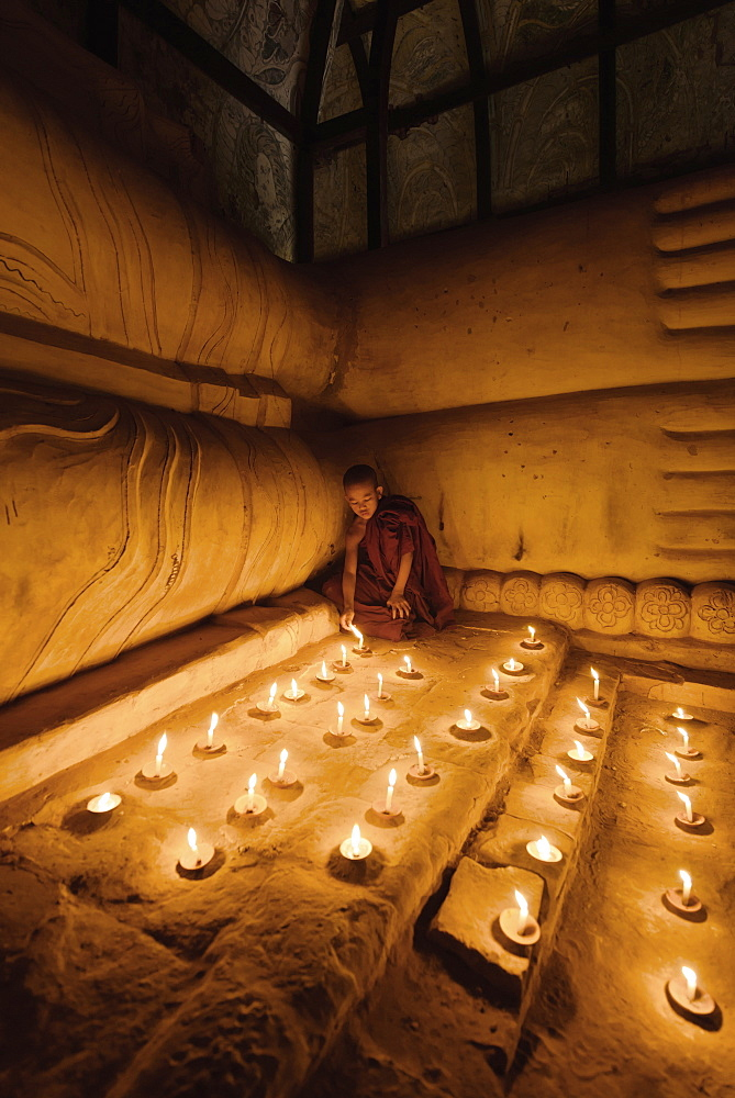 Asian monk lighting candles in temple