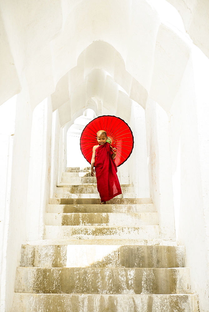 Asian Buddhist monk carrying umbrella on staircase at Hsinbyume Pagoda, Mandalay, Sagaing, Myanmar