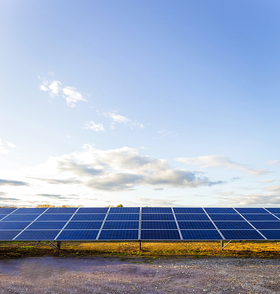 Solar panels under blue sky in remote landscape
