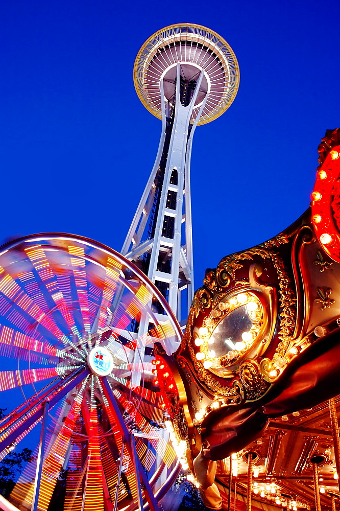 Low angle view of Space Needle, ferris wheel and carousel under night sky, Seattle, Washington, United States