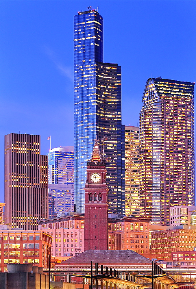Clock tower and illuminated high rise buildings in Seattle city skyline, Washington, United States