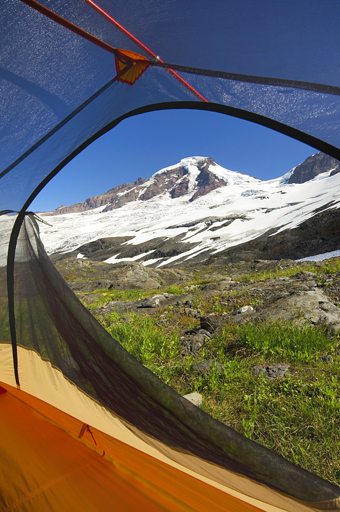 View from tent under snowy mountainside, North Cascades, Washington, USA