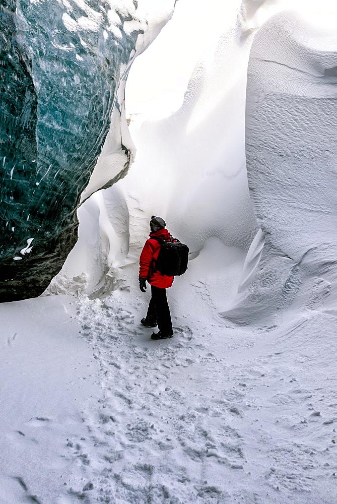 Hiker walking in snowy ice cave, Jokulsarlon, Iceland