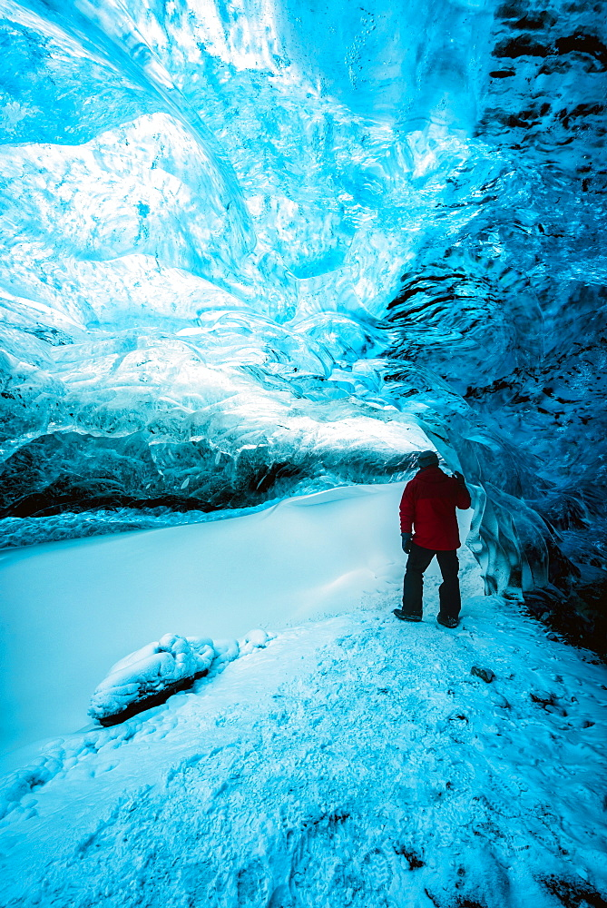 Hiker walking in ice cave, Jokulsarlon, Iceland
