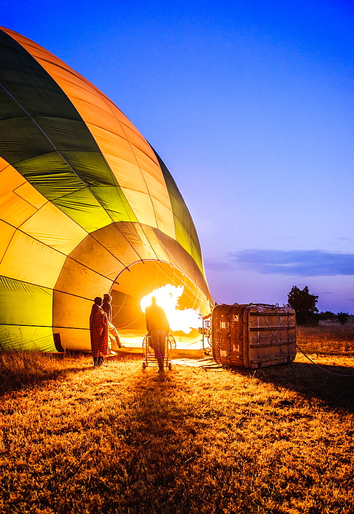 Hot air balloon inflating in rural field, Kenya, Africa