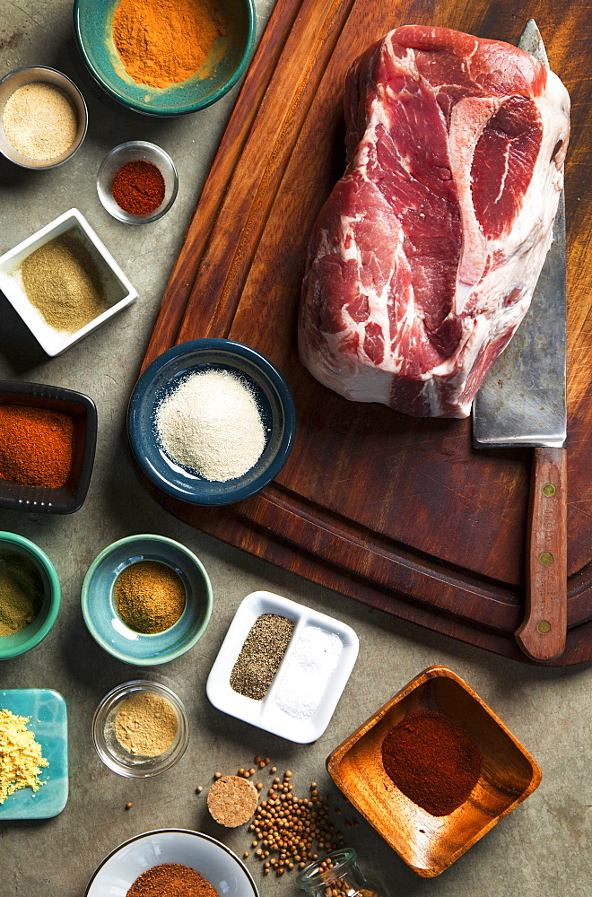 Cutting board with pork shoulder and variety of spices, Seattle, Washington, USA
