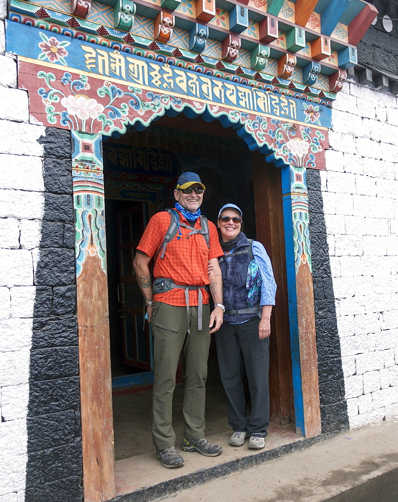 Caucasian couple standing in ornate doorway, Lukla, Khumbu region, Nepal