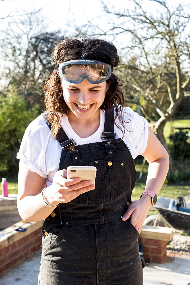 Smiling woman wearing dungarees and protective goggles checking her mobile phone, Oxfordshire, England