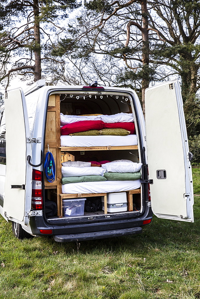 Rear view of camper van parked on a meadow, stacks of mattresses and bedding in back of vehicle, Oxfordshire, England