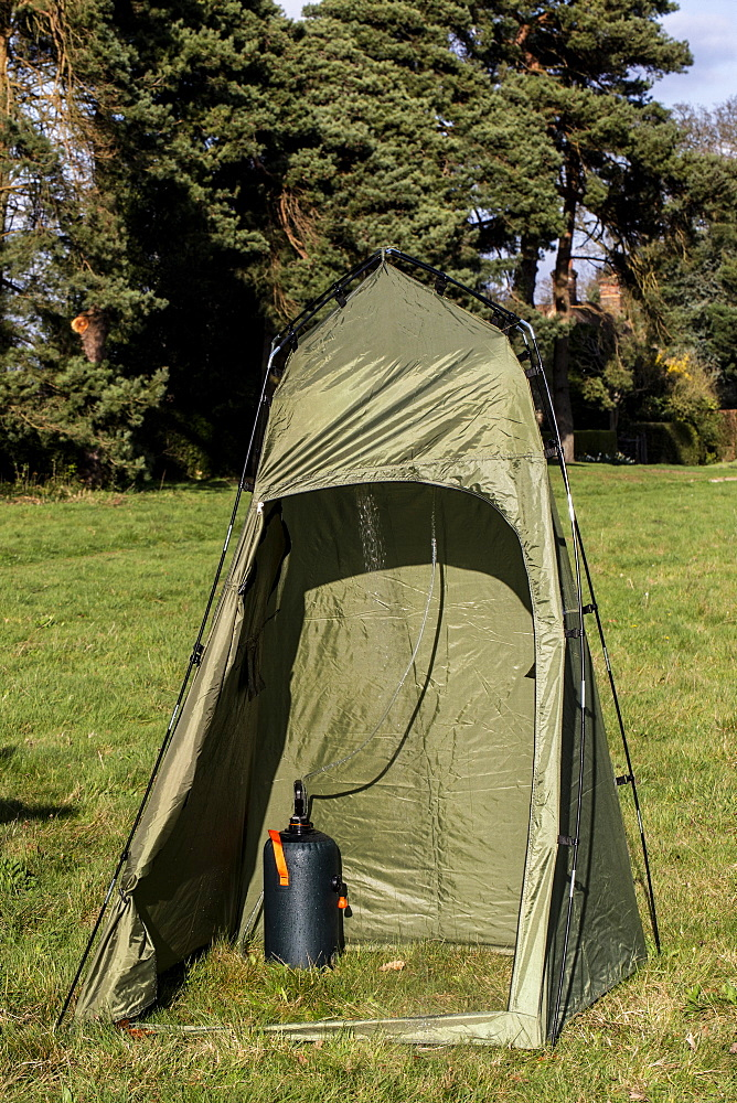Green shower tent pitched on a meadow, Oxfordshire, England