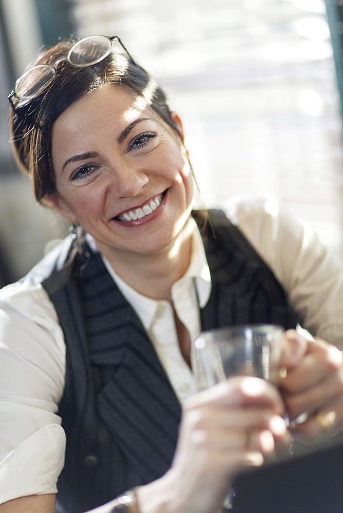 A woman holding a glass and smiling at the camera. A working lunch, New Hope, Pennsylvania, USA